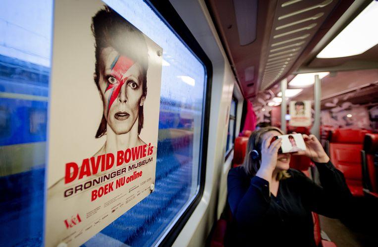 Treinreizigers maken een virtuele reis door het leven van de Britse popster David Bowie, die wordt vertoond in een 'Virtual Bowie Coupé'. De treincoupé is ingericht in samenwerking met het Groninger Museum, waar een tentoonstelling te zien is over muziekicoon Bowie. Beeld anp