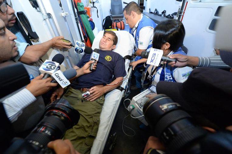 José Alvarenga wordt dinsdagavond na terugkeer in zijn thuisland El Salvador bestormd door media onderweg naar de ambulance die hem naar een ziekenhuis zal brengen Beeld AFP