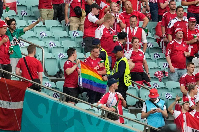 Beveiligers grijpen in als Deense supporters met een regenboogvlag zwaaien in het stadion van Bakoe. Beeld AFP