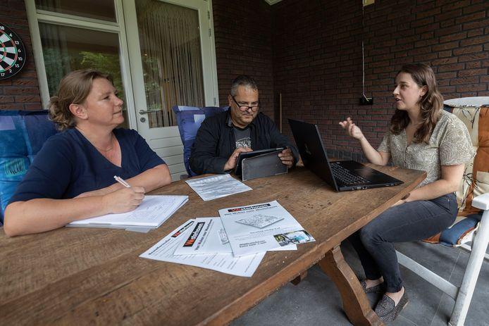Angelique van Kruijsdijk (l), Gerwin van Ampting en Anne Kuijlaars leggen de laatste hand aan de verhalen voor het boek 'Van Wuhan naar Westerhoven'.