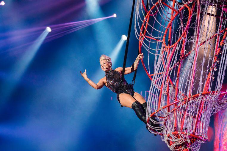 Pink beweegt zich tijdens haar wereldtoernee in 2019, vastgesnoerd in een ingenieuze kabelconstructie, over de hoofden van de menigte op de vloer. Beeld Getty Images
