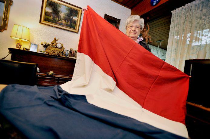 Wies Brokken-Van Erven in 2010 met de vlag die ruim 65 jaar in de linnenkast lag.