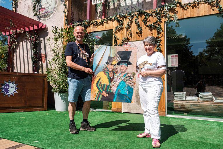 Monique Hertleer geeft een schilderij af aan Ivo Corbeels van het Buurthuis.