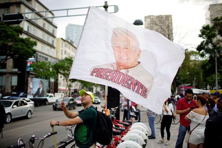 Een aanhanger van presidentskandidaat Andres Manuel Lopez Obrador zwaait met een vlag met diens beeltenis en daaronder de benaming 'president'. Beeld REUTERS