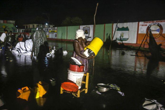 Een vrouw staat met haar voeten in het water nadat de tropische storm Grace voor hevige regenbuien heeft gezorgd boven het vluchtelingenkamp in Les Cayes waar Haïtianen getroffen door de zware aardbeving van dit weekend opgevangen worden.