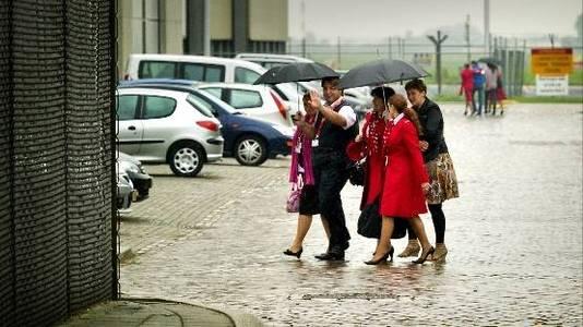 Medewerkers van Martinair verlaten donderdag het kantoor na afloop van een bijeenkomst op Schiphol Oost. Het rode pakje wordt blauw: KLM neemt alle cabinepersoneel en passagiersvluchten over. ( ANP)
