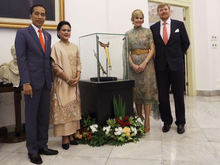 De Indonesische president Joko Widodo en zijn vrouw, koning Willem-Alexander en koningin Máxima bij een vitrine met de kris die Nederland heeft teruggegeven. Beeld AP