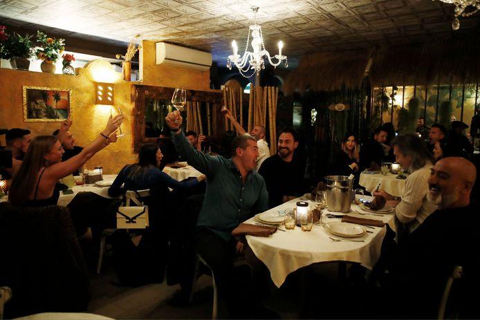 Klanten toasten vrijdagavond in een restaurant in Milaan.