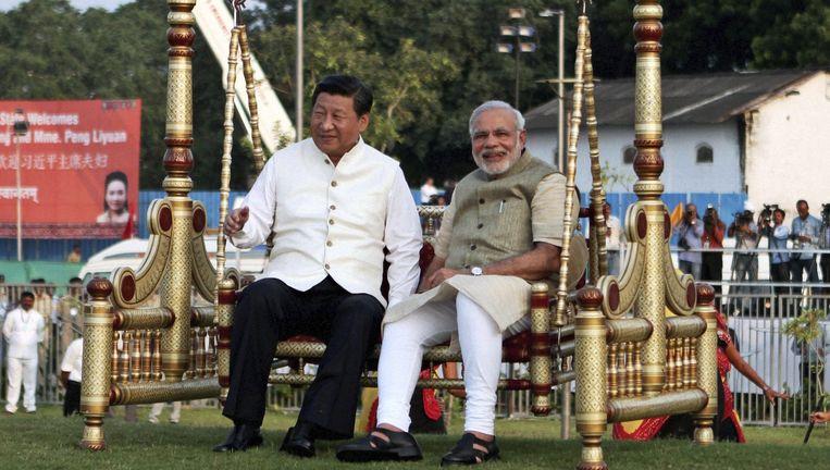 De Chinese president Xi Jinping (links) en de Indiase premier Narendra Modi zitten op een traditionele schommel in de Indiase stad Ahmadabad. Xi bracht vorige week een driedaags bezoek aan India. Beeld AP