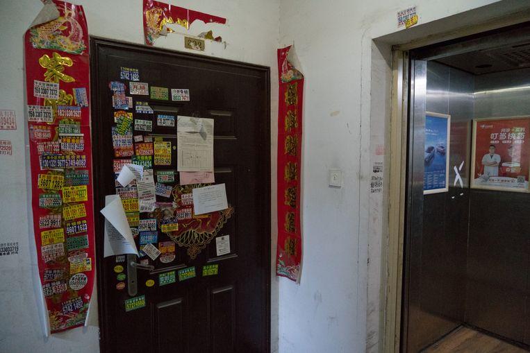De deur van nummer 14-3-202, het onheilshuis. Op en naast de voordeur zijn allemaal aanmaningen geplakt. Beeld Ruben Lundgren
