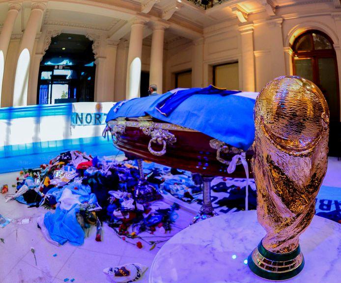 Het opgebaarde lichaam van Maradona in het paleis in Buenos Aires. De wereldbeker, die hij zijn land in 1986 schonk, staat er naast.