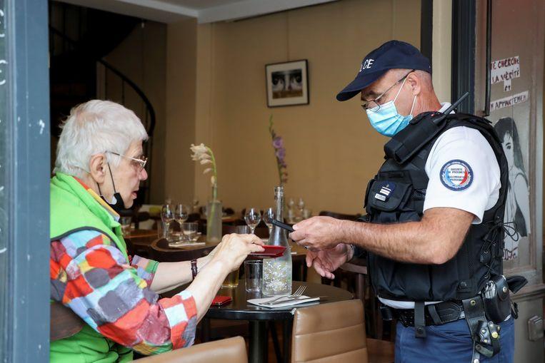Een politieagent controleert de pass sanitaire van een restaurantgast in Parijs. Beeld REUTERS