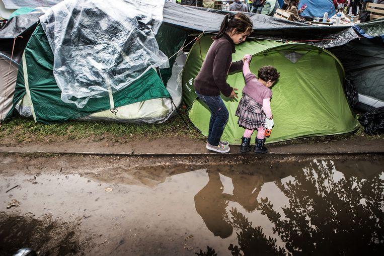 Vluchtelingen in het uitgeregende kamp. Als straks de temperaturen dalen, wordt de toestand helemaal onhoudbaar. Beeld Bob Van Mol