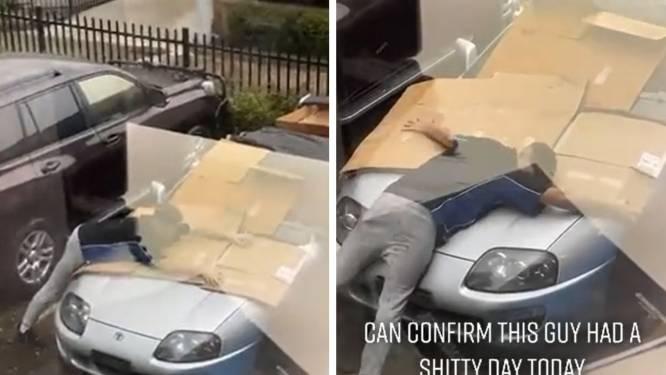 Il tente de sauver sa voiture de la grêle... en se couchant dessus avec des cartons