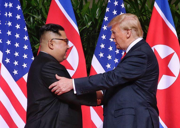 De Noord-Koreaanse leider Kim Jong-un en VS-president Donald Trump schudden elkaar de hand bij het begin van een historische top op Sentosa-eiland in Singapore, 12 juni 2018. Beeld EPA