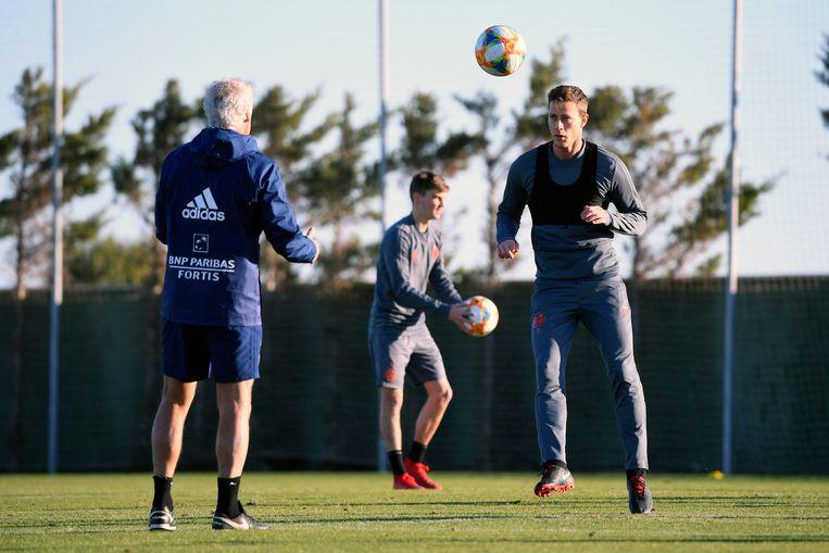 Verdediger James Lawrence kopt de bal terug naar zijn coach. Beeld Photo News