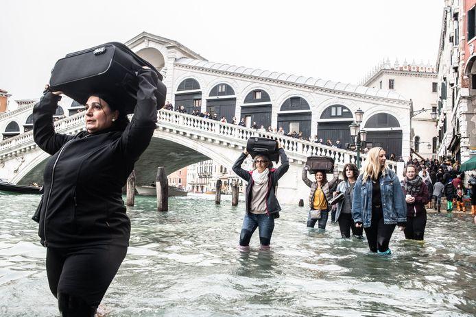 Mensen dragen hun bagage boven het hoofd in Venetië bij de Rialtobrug.