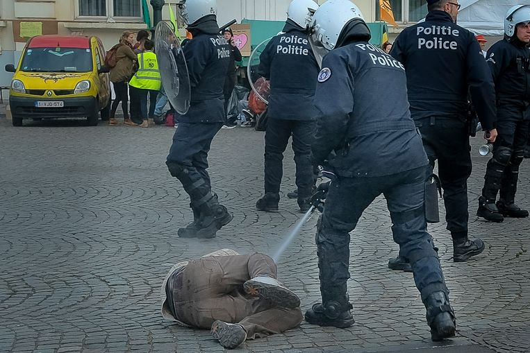 Op een foto die onze fotograaf maakte en op beelden van VTM Nieuws is bijvoorbeeld te zien hoe de politie de spray inzet tegen manifestanten die op de grond liggen en schijnbaar geen bedreiging vormen. Eén man was zelfs al geboeid. Beeld Baert Marc