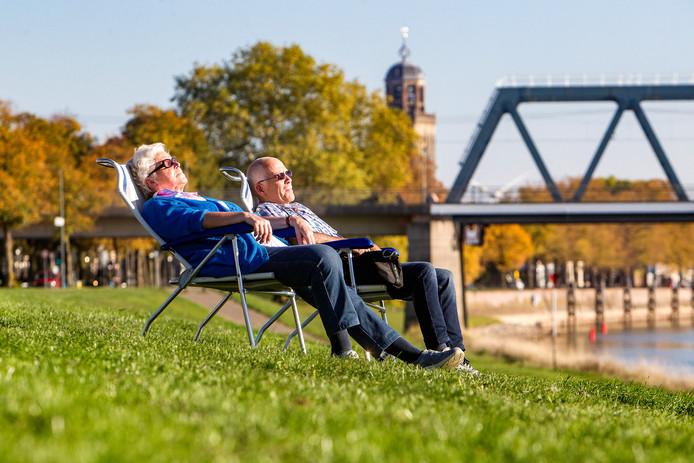 13 oktober 2018 en het is zomers warm. Zonaanbidders genieten in Deventer langs de IJssel.