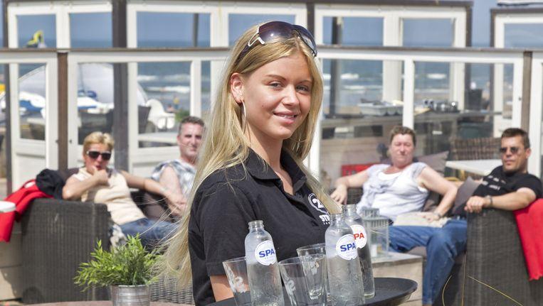 Een meisje werkt in een strandtent tijdens de zomer. Beeld anp
