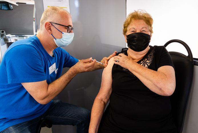 Mensen laten zich vaccineren in een prikbus.