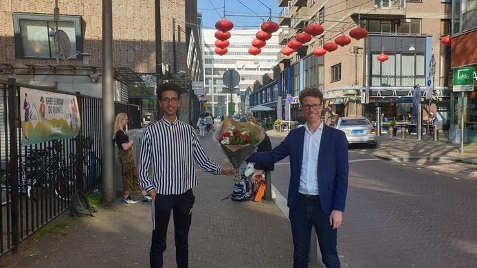 Martijn Balster krijgt als kersvers lijsttrekker van PvdA Den Haag bloemen van overhandigd van bestuurslid Abderrazzak Afkyr.