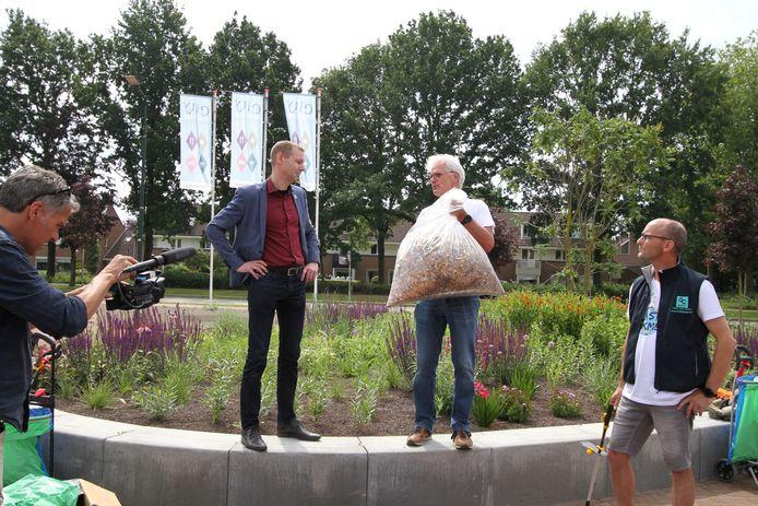 Harry Welp, voorzitter van Stichting GoClean Veldhoven, overhandigt de zak met peuken aan wethouder Jeroen Rooijakkers.