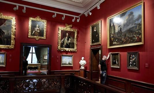 Een werknemer legt de laatste hand aan de schilderijen in het vernieuwde Mauritshuis.