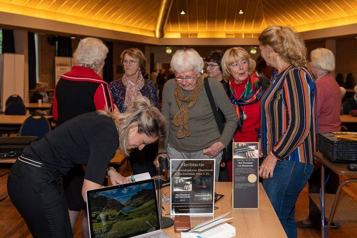Angelique van der Bijl zet haar handtekening in haar boeken Nachtschade en Het Weeskind van Haamstede in De Schutse