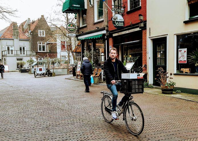 Jon Cornelese fiets door Delft, in betere tijden. Achieffoto.