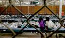 Twee meisjes kijken in een opvangcentrum in Nogales, Arizona, naar een wedstrijd tijdens het WK Voetbal van 2014