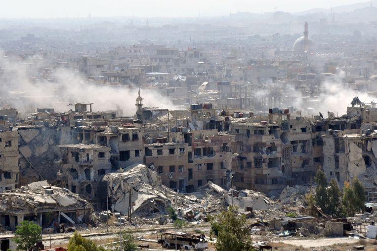 Rook is te zien boven het Yarmouk-kamp nabij Damascus. Het Syrische leger bombardeert de plek.  Beeld null