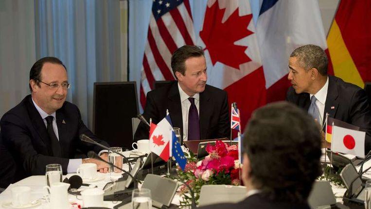 De Franse president Francois Hollande (links), naast de Britse premier David Cameron (midden) en de Amerikaanse Barack Obama (rechts), gisteren tijdens een bijeenkomst van de G7. Beeld afp