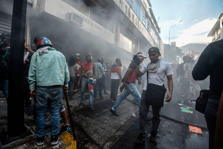 Actievoerders steken een kantoor van de verkeerspolitie in brand tijdens protesten tegen de verkiezingen in Caracas gisteren. Beeld afp