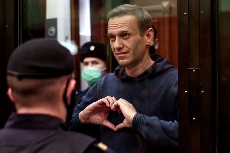 Aleksej Navalny maakt in de rechtszaal een hartvormig gebaar. Hij keert zich nadrukkelijk tegen sancties die niet zozeer het Poetin-regime treffen, maar vooral de bevolking. Beeld AFP