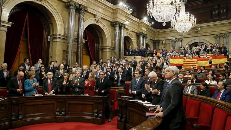 Terwijl de separatistische partijen applaudisseren, steekt oppositiepartij PP Spaanse, maar ook Catalaanse vlaggen omhoog. Beeld REUTERS
