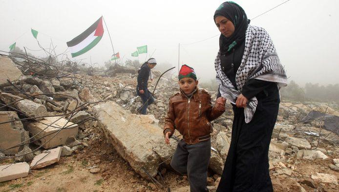 De vrouw van beschuldigde Raid Masalmeh bij de resten van haar vernietigde woning.