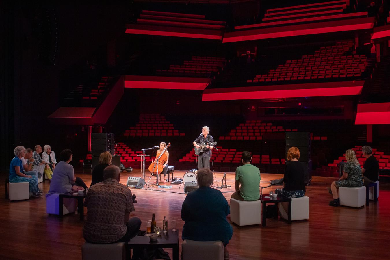 Spinvis treedt op in de grote zaal van het Chassé Theater als onderdeel van het Laat Licht Festival. De 30 bezoekers zitten op het podium en de stoelen in de zaal zijn allemaal leeg.