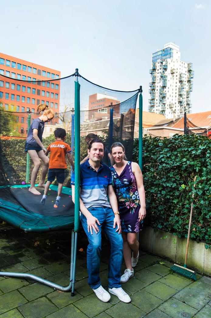 Erik en Marleen de Ridder met op de achtergrond hun kinderen op de trampoline.