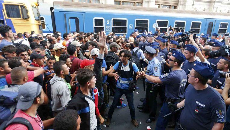 Asielzoekers botsen op een muur van politie in het station van Boedapest. Beeld REUTERS