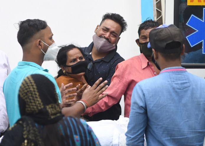 Nabestaanden rouwen bij een ziekenhuis in New Delhi.