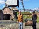 Ludo Helsen en Leo Struyven dragen een oude bierton op weg naar de nieuwe locatie van het Geels Brouwerijmuseum naast het Bakkerijmuseum en de molen.