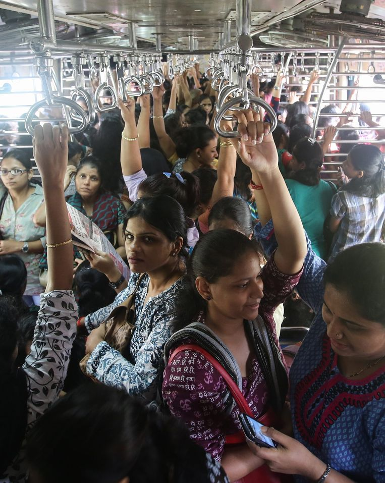 Indische vrouwen reizen per trein naar hun werk in Mumbai, India. Beeld EPA