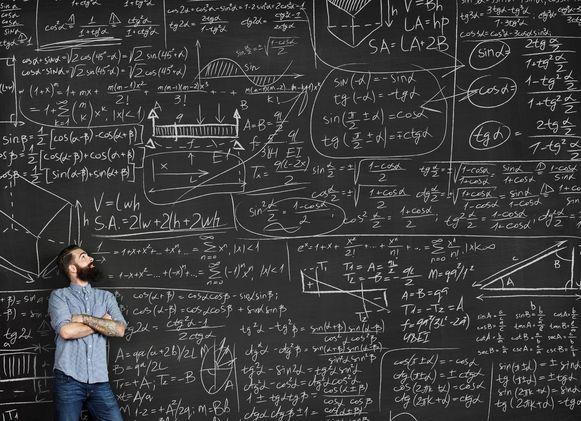 Een man voor een schoolbord vol met wiskundige formules.