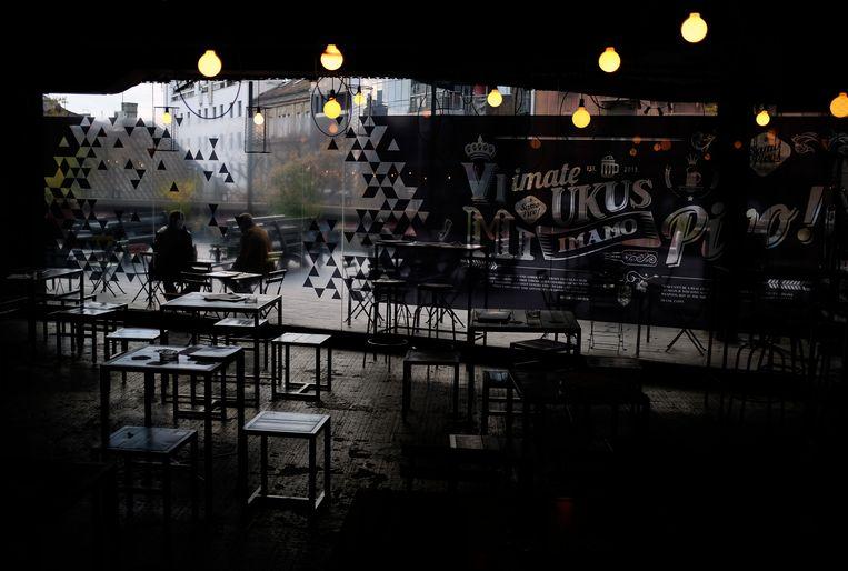 Bezoekers in een verder nagenoeg leeg café in het centrum van Belgrado.  Beeld AP