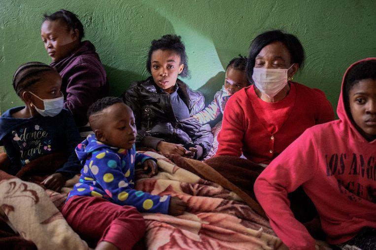 Ntombi Zodwa (rode trui), in haar huis zonder elektriciteit in Soweto. Beeld Luca Sola
