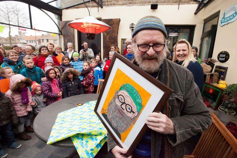 Willem Vermandere is dolblij met het portret dat kinderen van de dorpsschool De kleine reus maakten.