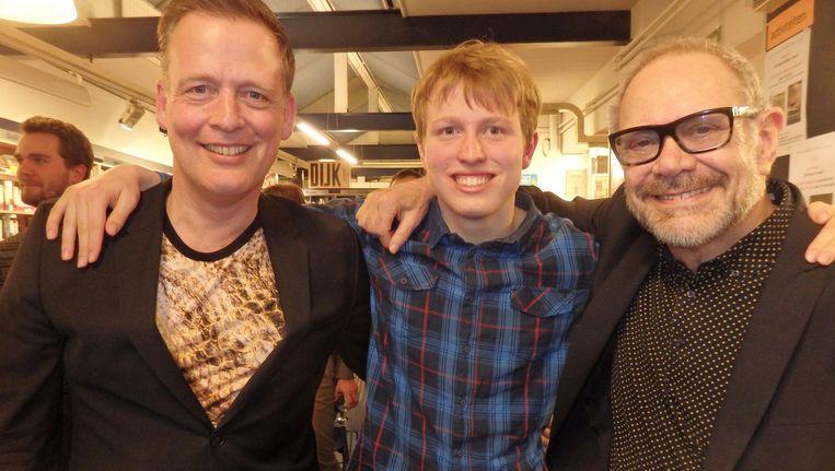 Auteur Erik Jan Harmens, zijn zoon Julian en zanger Rob de Nijs, die het eerste exemplaar van Pauwl in ontvangst nam Beeld Schuim