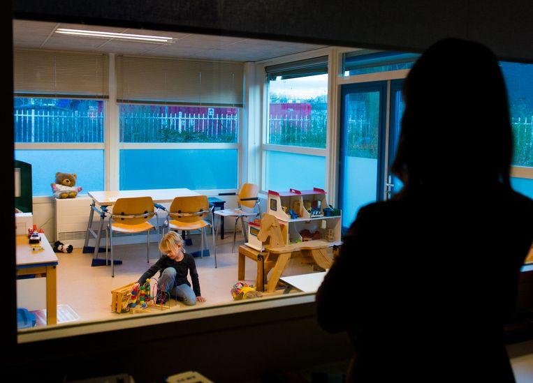Een jeugdhulpverlener observeert het gedrag van een meisje door een spiegelwand.  Beeld ANP XTRA