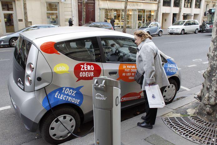 Een vrouw bekijkt een Bluecar in Parijs in 2011.